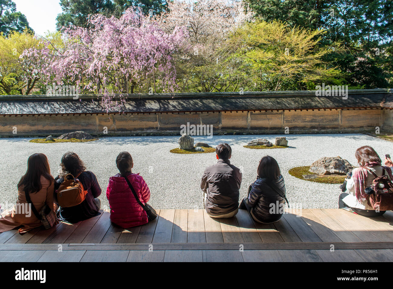 Japanese tourists enjoy tranquility at Ryoanji Temple in Kyoto, Japan. This Zen Buddhist temple is famous for its rock garden. Stock Photo