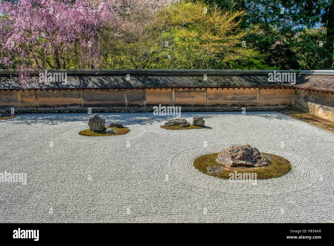 Japanese tourists enjoy tranquility at Ryoanji Temple in Kyoto, Japan. This Zen Buddhist temple is famous for its rock garden. - Stock Image