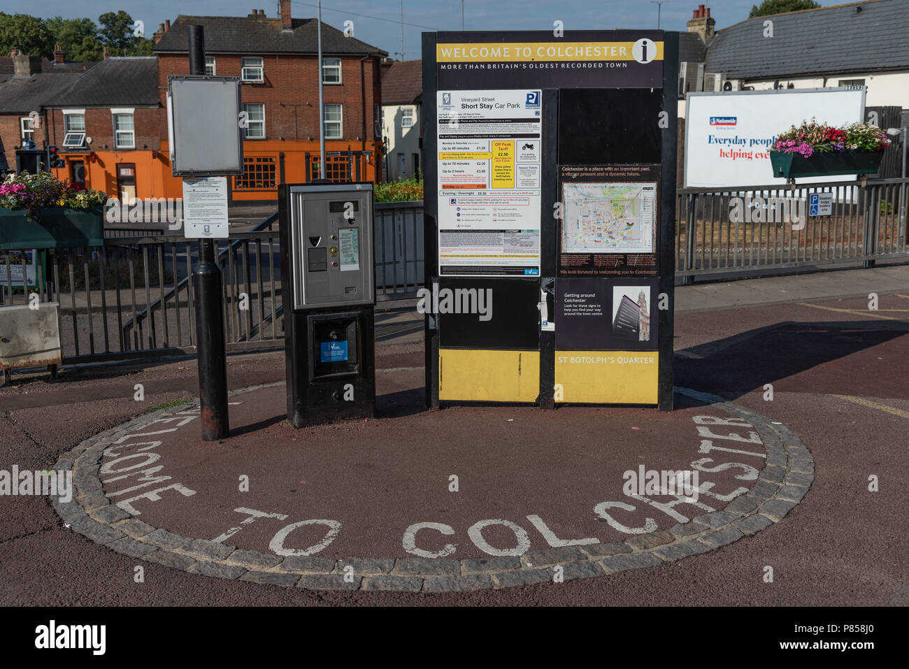 Welcome to Colchester! Vinyard Street Short Stay Car Park list of daily charges and ticket dispenser in early morning sun light. - Stock Image