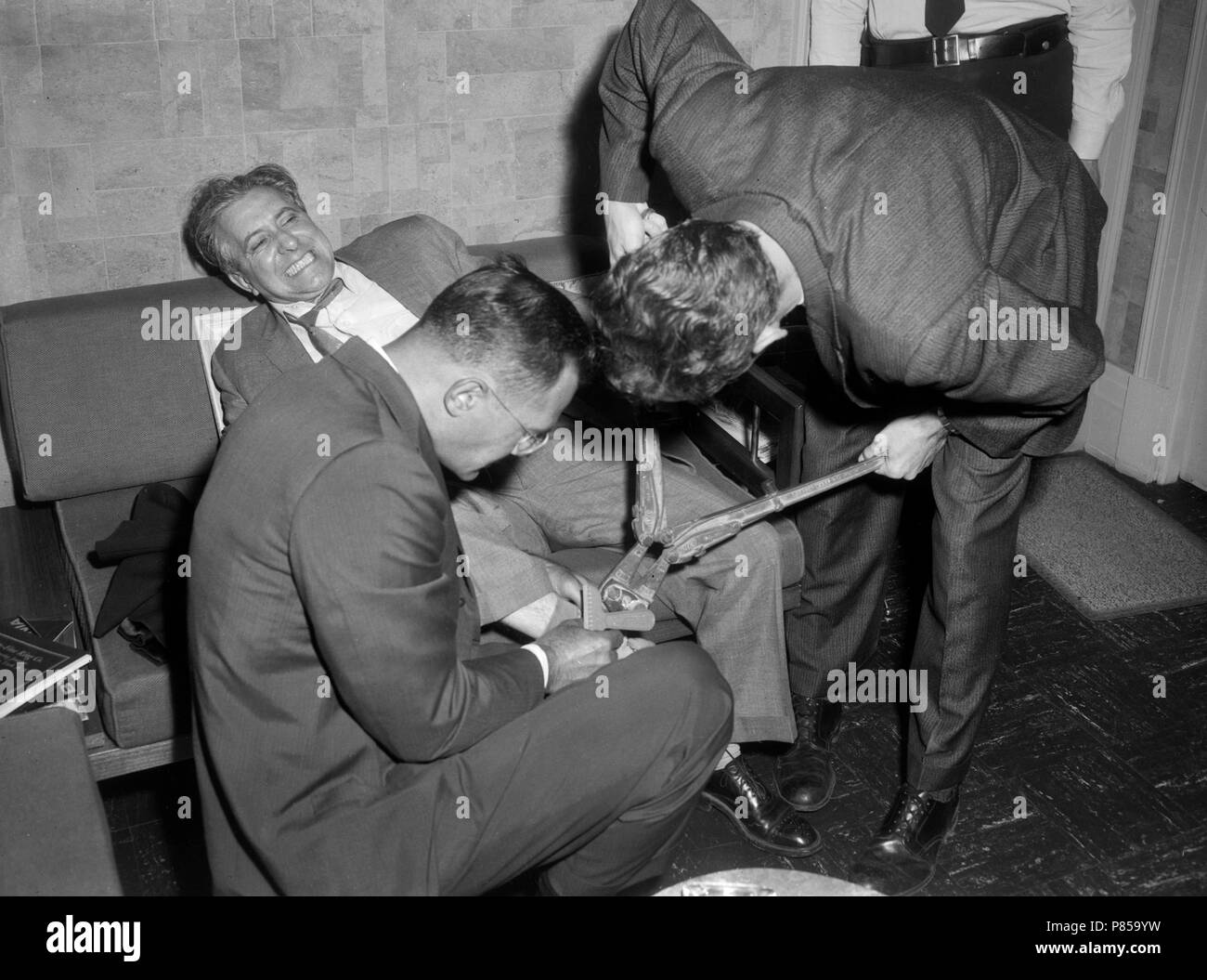 A jeweler grimaces as police cut him loose after a bad guy had handcuffed him to a couch during a robbery in Chicago, ca. 1962. - Stock Image