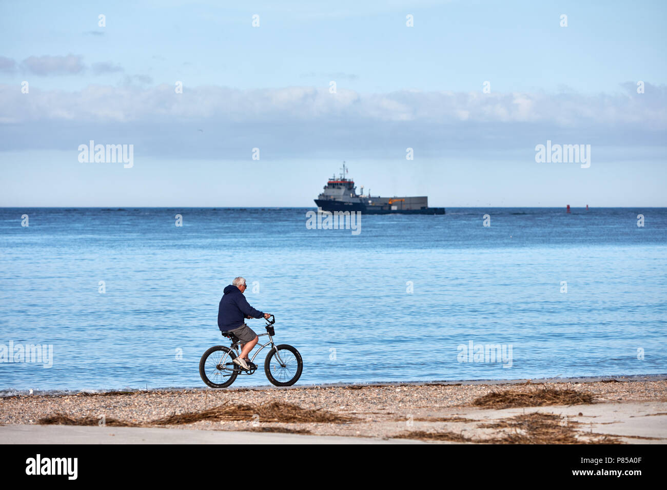 Man riding a bike on the beach as a US Navy ship sails past Stock Photo