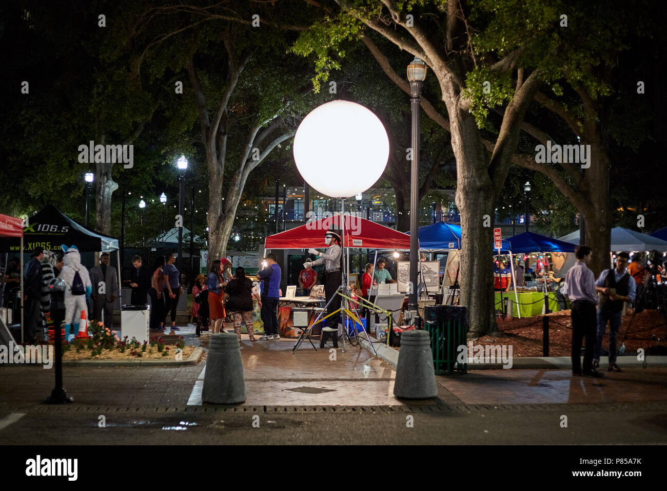 Street artist performing under a glowing orb at First Wednesday Art Walk in Jacksonville, Florida, on February 7, 2018. - Stock Image