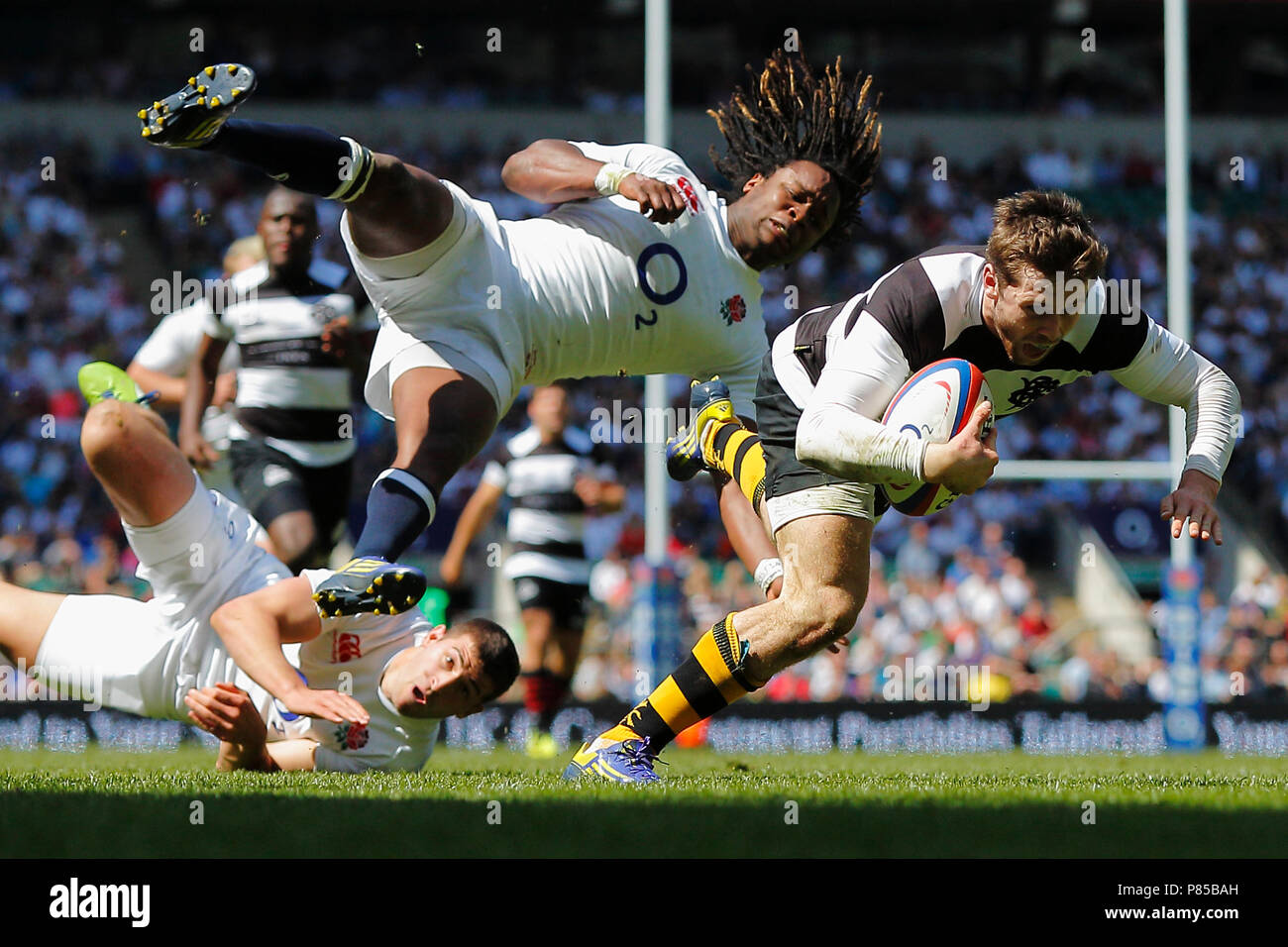 Elliot Daly fends of the tackle from Marland Yarde to score a try for the Barbarians during the England vs Barbarians match, at Twickenham Stadium, London. 26 May 2013 --- Image by © Paul Cunningham - Stock Image