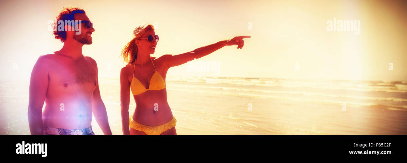 Woman gesturing while holding man hands at beach - Stock Image