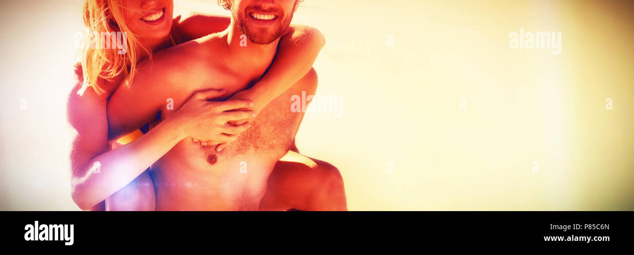Portrait of young man piggybacking beautiful woman at beach - Stock Image