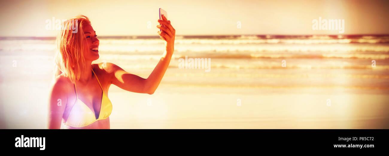 Happy young woman in yellow bikini taking selfie at beach - Stock Image