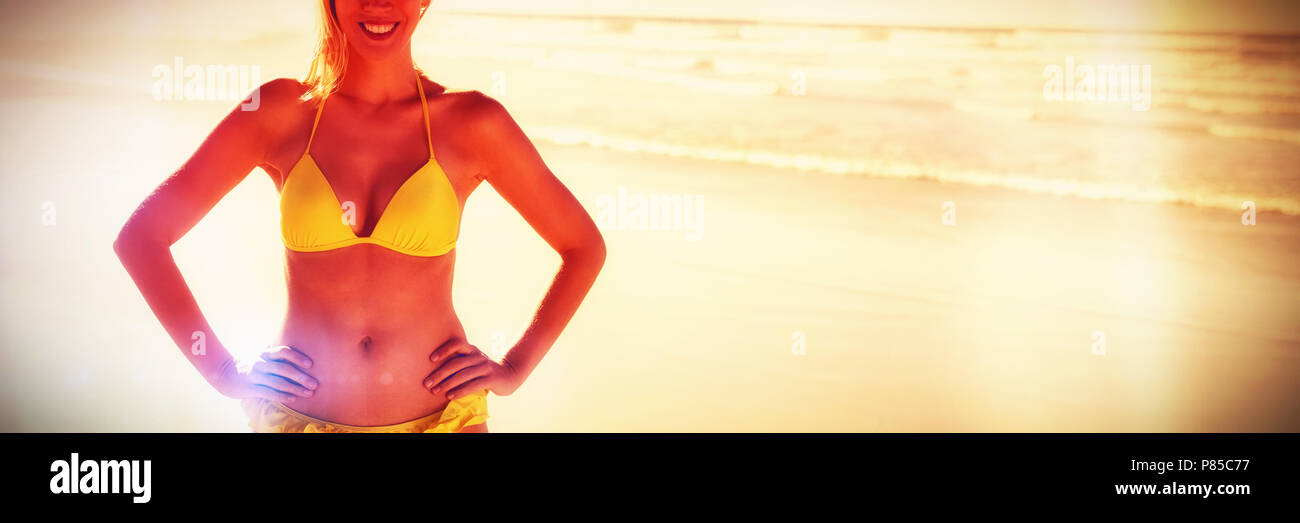 Portrait of smiling young woman in yellow bikini standing at beach - Stock Image