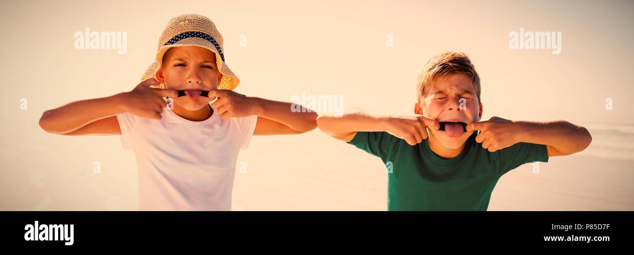 Siblings making teasing faces at beach - Stock Image