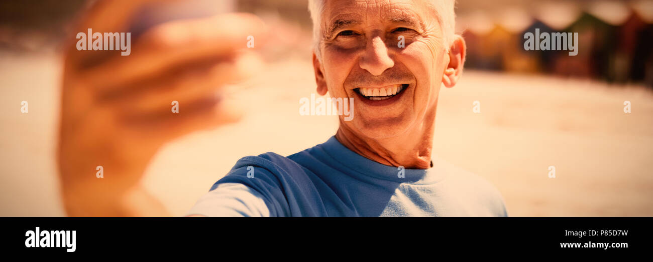 Happy senior man taking selfie at beach - Stock Image