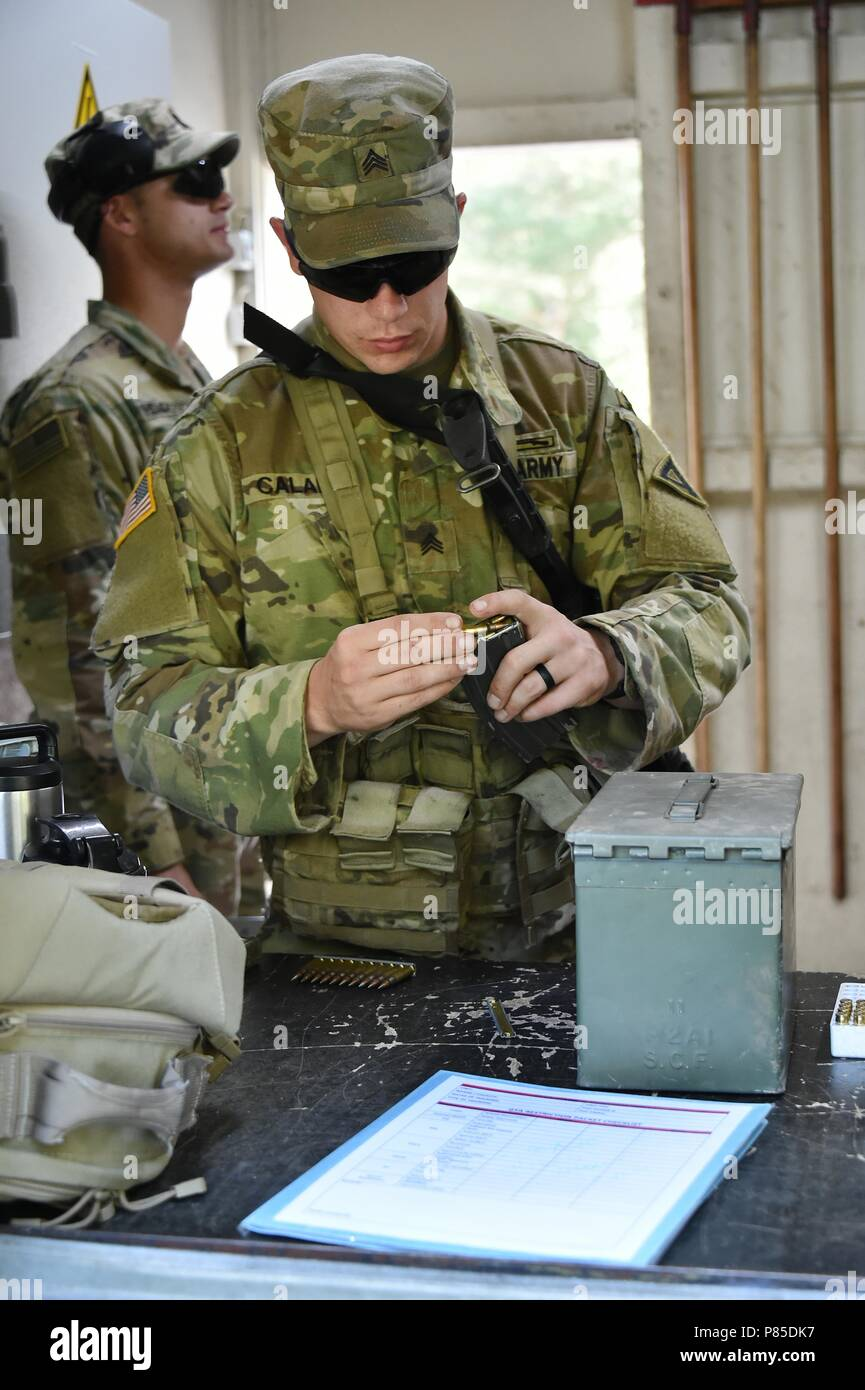 U.S. Army Sgt. Christian Calame assigned to 1st Battalion, 4th Infantry Regiment, 7th Army Training Command (7th ATC) receives ammunition for the stress shoot lane as part of the 7th ATC Best Warrior Competition, Grafenwoehr Training Area, Germany, June 20, 2018, June 20, 2018. The three-day event ends June 21 with the announcement of the 7th ATC Officer, Noncommissioned Officer and Soldier of the Year. The winners will move on to compete in the U.S. Army Europe Best Warrior Competition. (U.S. Army photo by Gertrud Zach). () Stock Photo