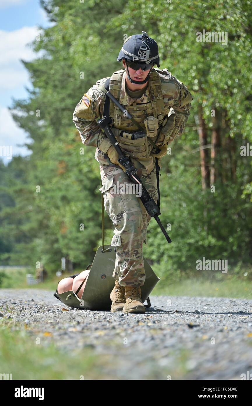 U.S. Army 1st Lt. Robert L. Martin assigned to 1st Battalion, 4th Infantry Regiment, 7th Army Training Command (7th ATC) pulls a simulated casualty on a sked litter during the stress shoot lane as part of the 7th ATC Best Warrior Competition, Grafenwoehr Training Area, Germany, June 20, 2018, June 20, 2018. The three-day event ends June 21 with the announcement of the 7th ATC Officer, Noncommissioned Officer and Soldier of the Year. The winners will move on to compete in the U.S. Army Europe Best Warrior Competition. (U.S. Army photo by Gertrud Zach). () - Stock Image