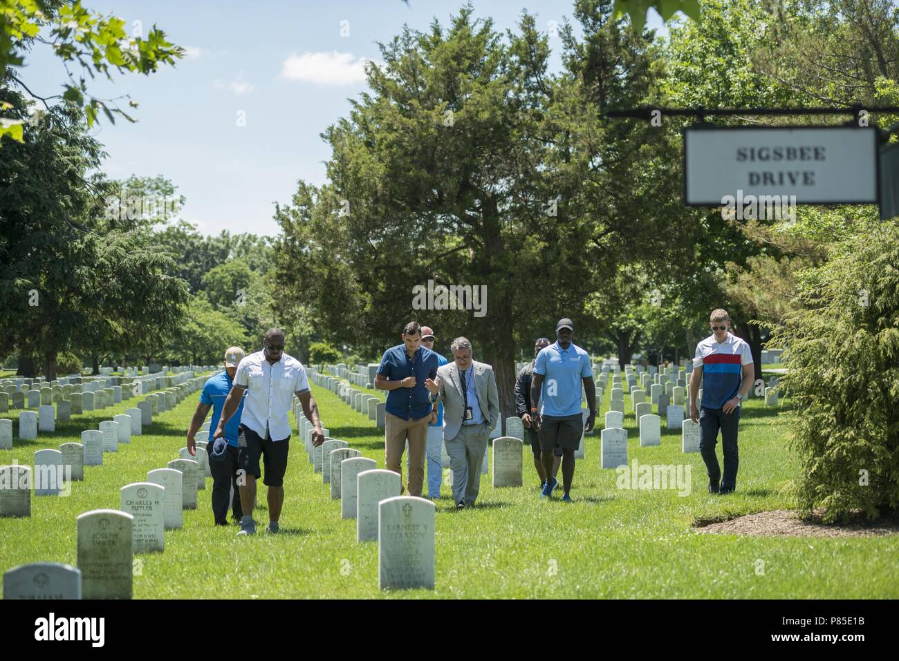 Rod Gainer (center), historian, Arlington National Cemetery, leads a tour with members of the Detroit Lions next to the Mast of the Maine in Section 23 of Arlington National Cemetery, Arlington, Virginia, June 12, 2018, June 12, 2018. The Lions visited Arlington National Cemetery to participate in an educational staff ride where they spoke with cemetery representatives, field operations, received a tour of the Memorial Amphitheater Display Room from ANC historians, and watched the Changing of the Guard Ceremony at the Tomb of the Unknown Soldier. (U.S. Army photo by Elizabeth Fraser / Arlingto - Stock Image