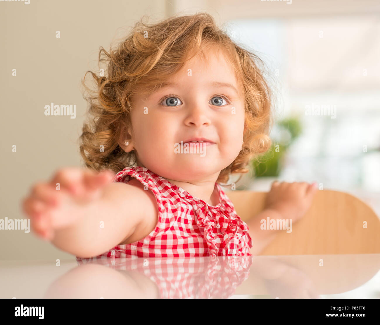 Beautiful blond child smiling asking for hold, wanting attention at home. - Stock Image