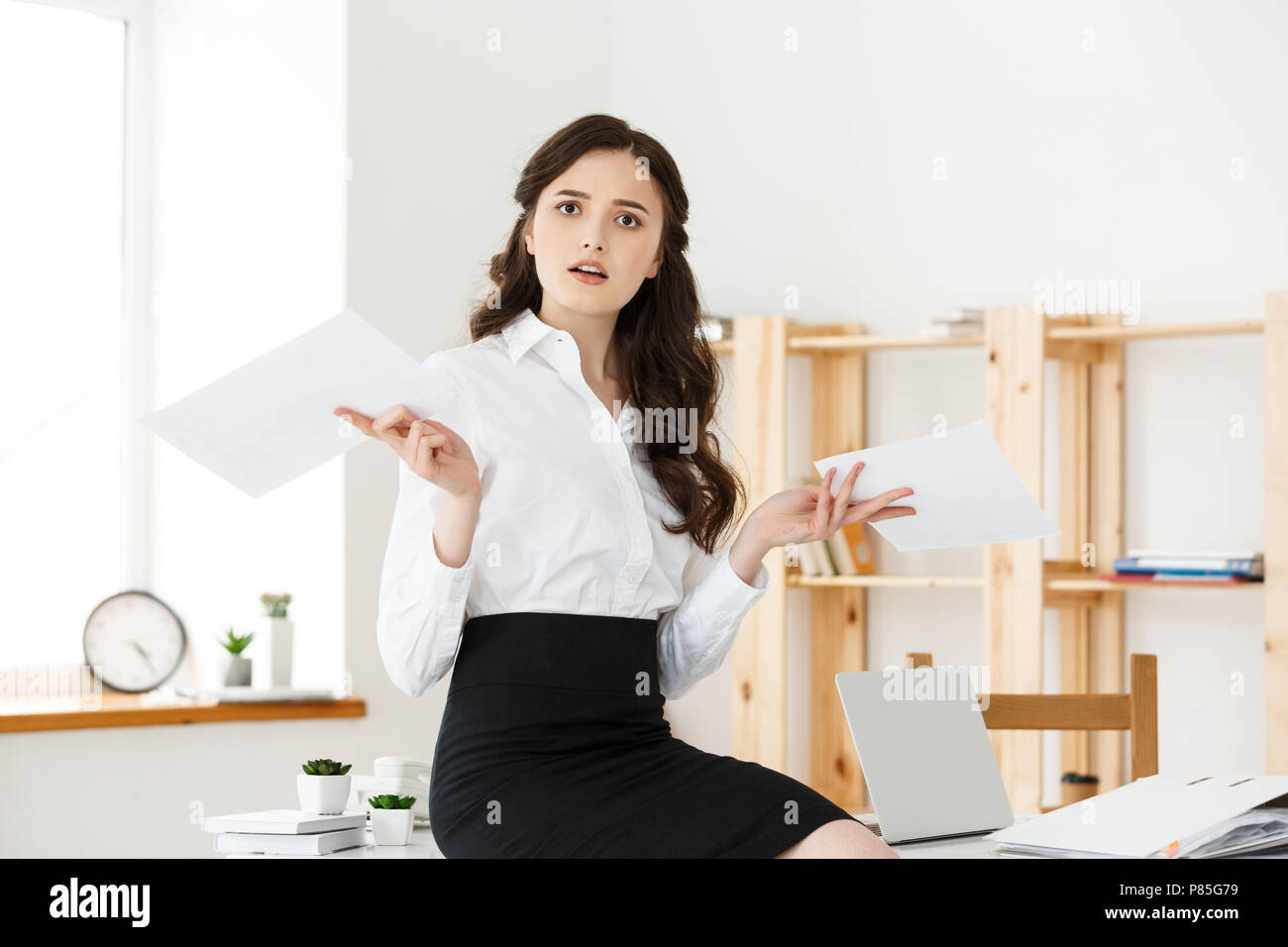 Shocked young business woman surprised by reading unexpected news in document, amazed woman office worker feeling stunned baffled by unbelievable information in paper about debt or dismissal - Stock Image