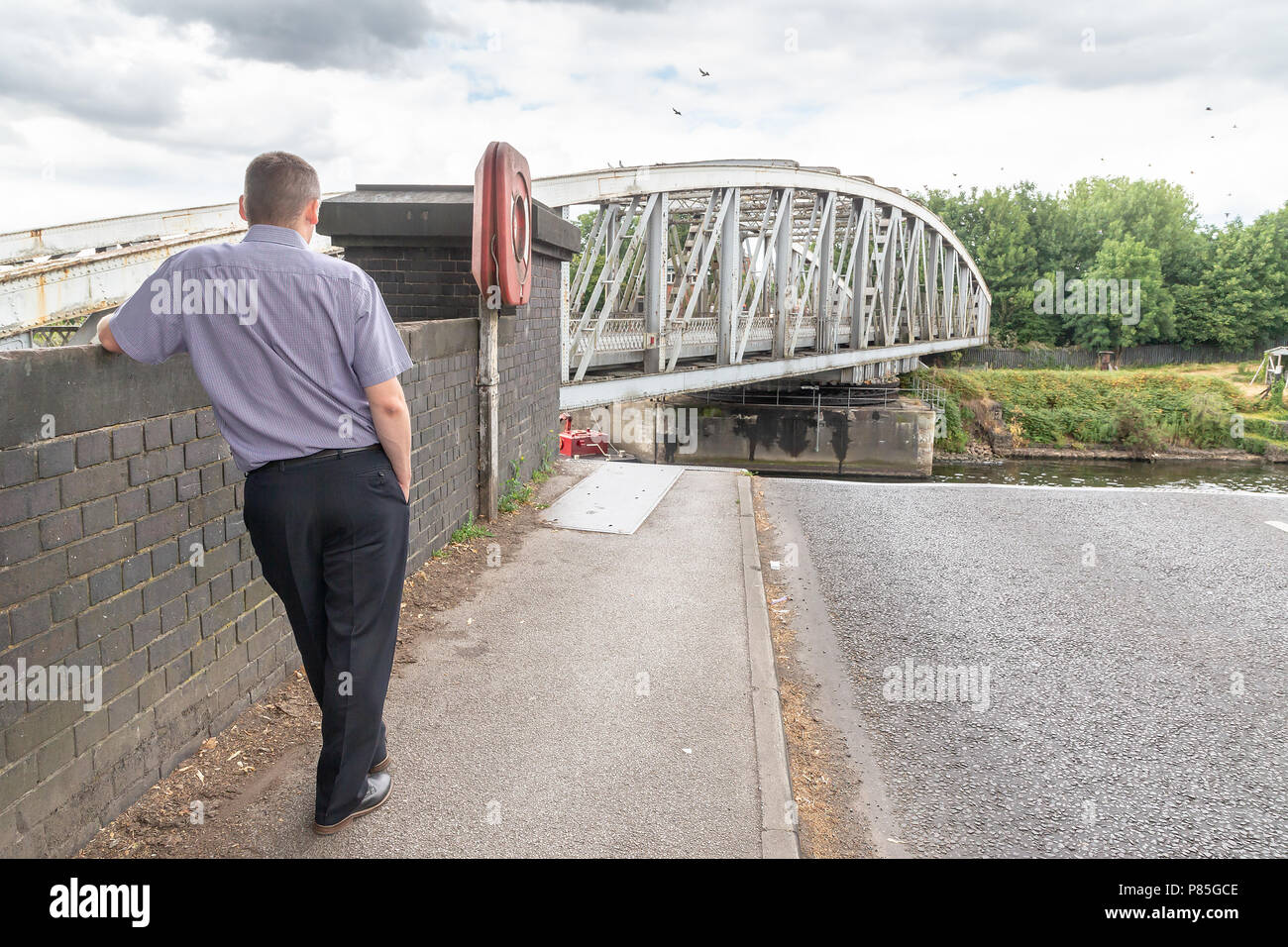 09-July 2018 - Male pedestrian leans against a wall and watches as Stockton Heath Swing Bridge closes after a ship has passed along the Manchester Shi - Stock Image
