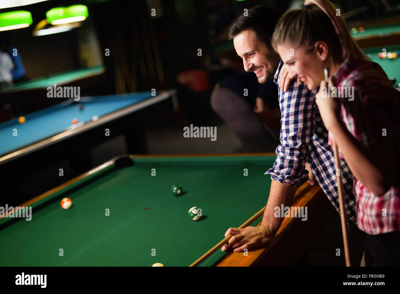 Young couple playing snooker together in bar - Stock Image