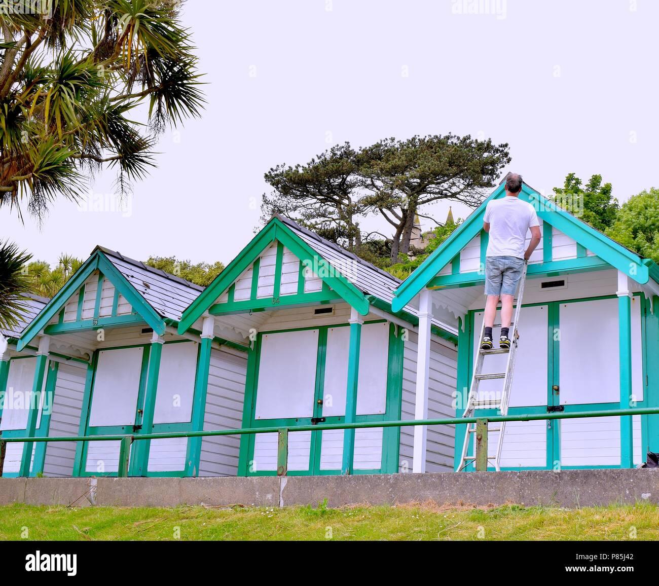 A man restoring his beach hut - Stock Image