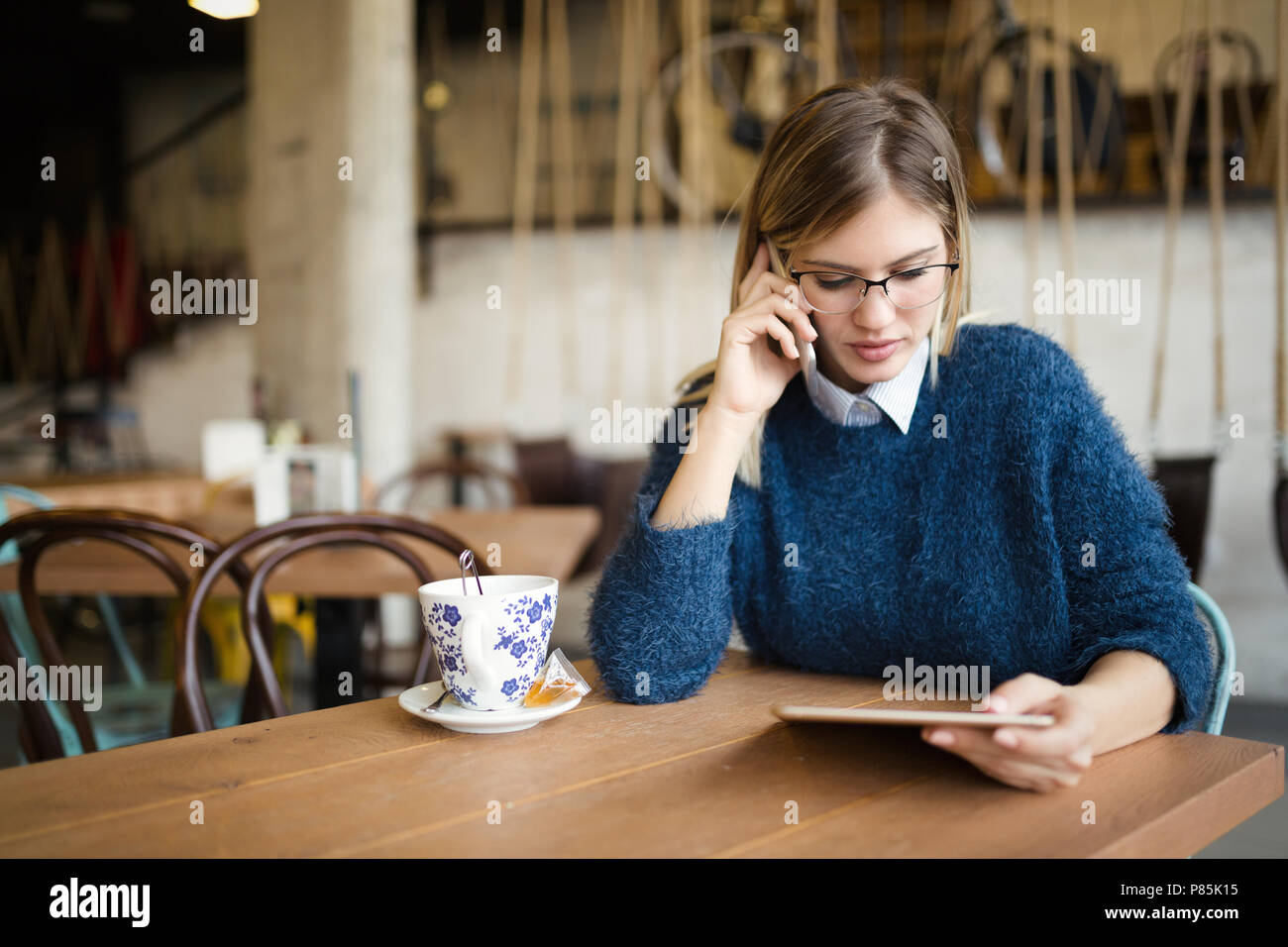 Portrait of busy businesswoman in coffee shop - Stock Image