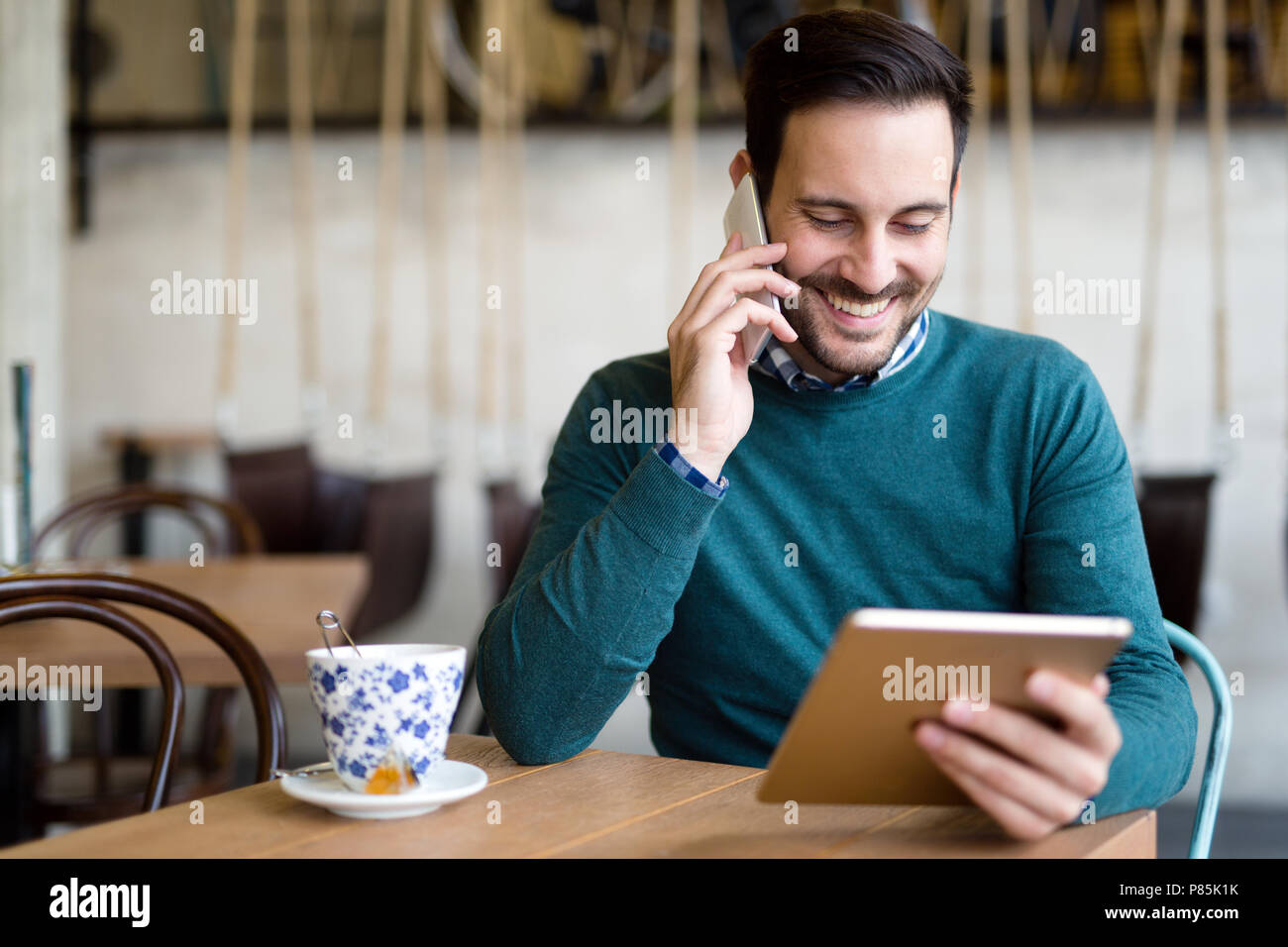 Portrait of busy businessman in coffee shop - Stock Image