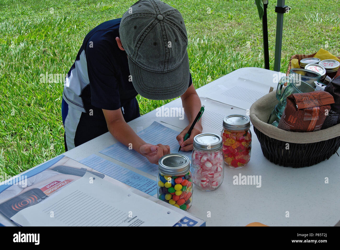 Silent auction table with candy count jars and kids guessing count - Stock Image