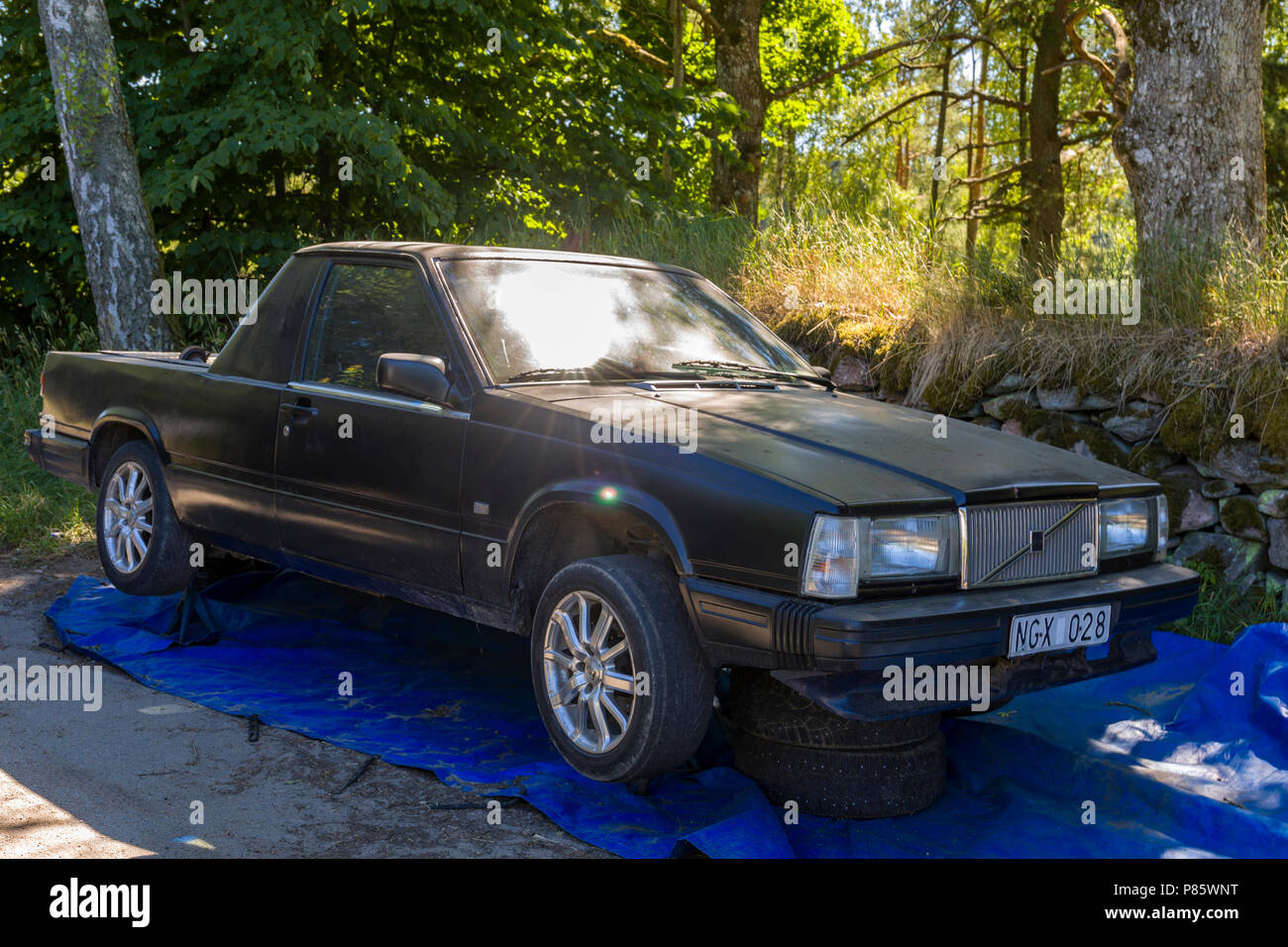 Old Volvo 740 sitting on car jack stands converted to a