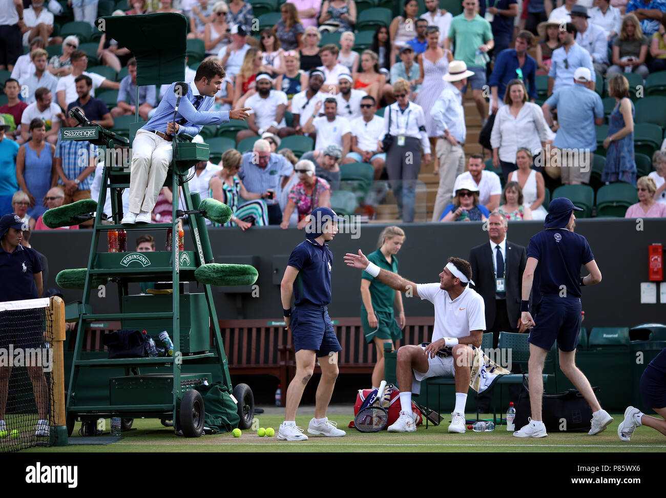 Juan Martin Del Potro speaks to the umpire after receiving a code violation on day seven of the Wimbledon Championships at the All England Lawn Tennis and Croquet Club, Wimbledon. - Stock Image