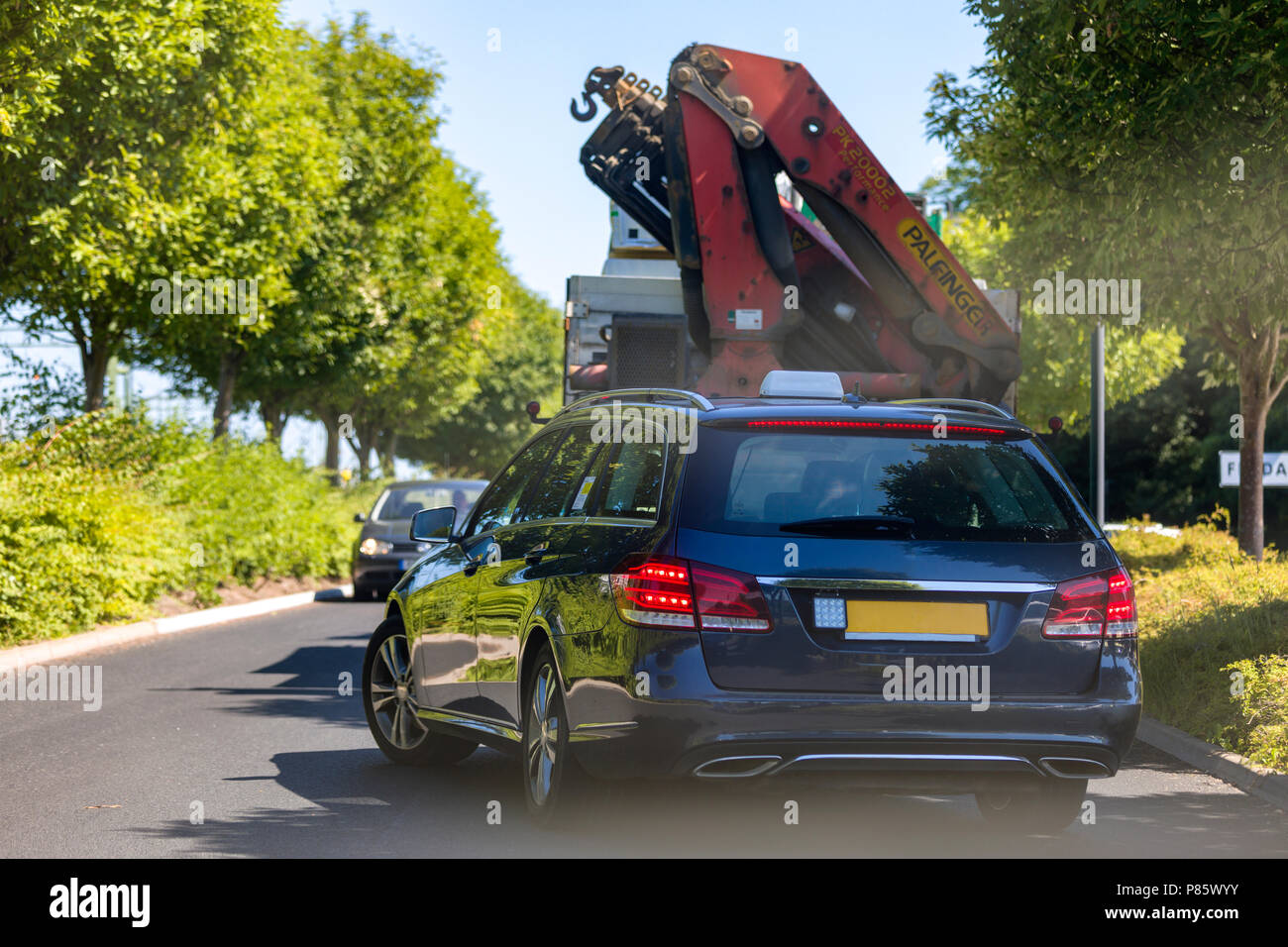 Car attempting to blindly overtake a large lorry that is blocking or stopping traffic Stock Photo
