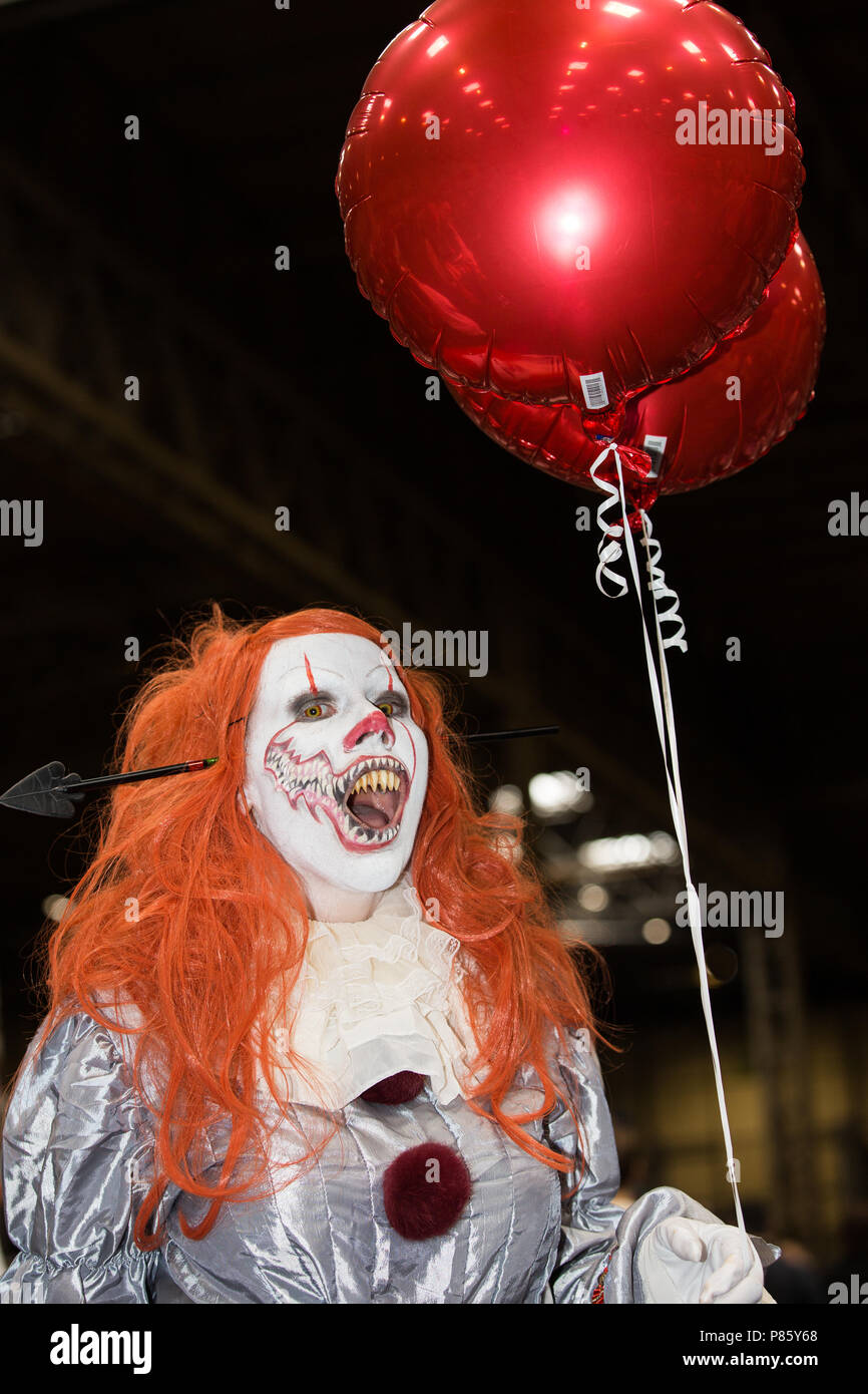 A female cosplayer dressed as Pennywise the clown from the Stephen King novel and movie IT at a comic con event in Birmingham, UK - Stock Image