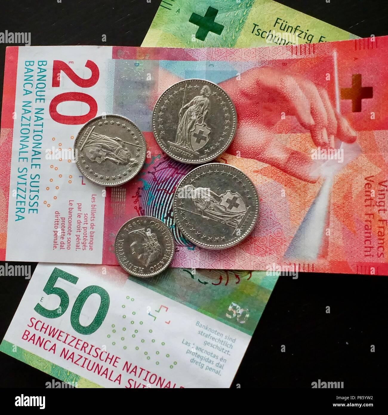 Swiss coins and bills on dark background. Currency used in Switzerland and Liechtenstein. - Stock Image