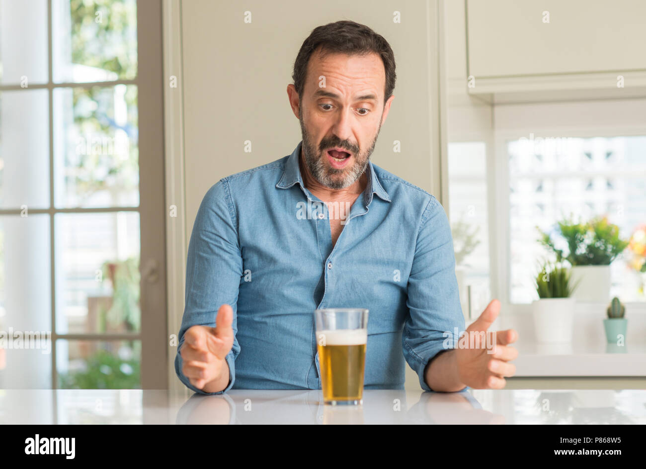 Middle age man drinking beer scared in shock with a surprise