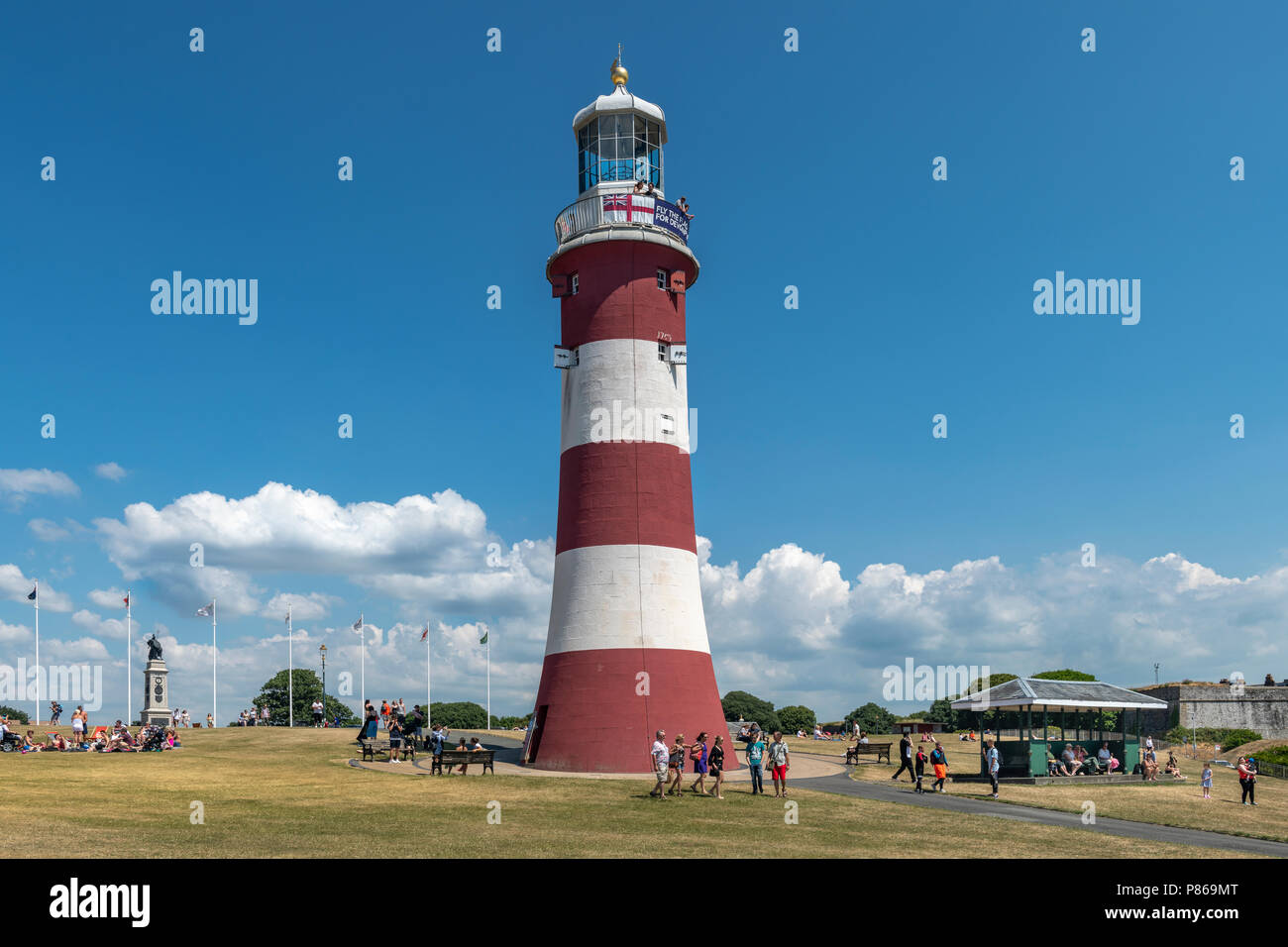 On yet another hot day in July, tourists wander around Smeaton's Tower on Plymouth Hoe seeking whatever shade they can find, as  temperatures in South - Stock Image