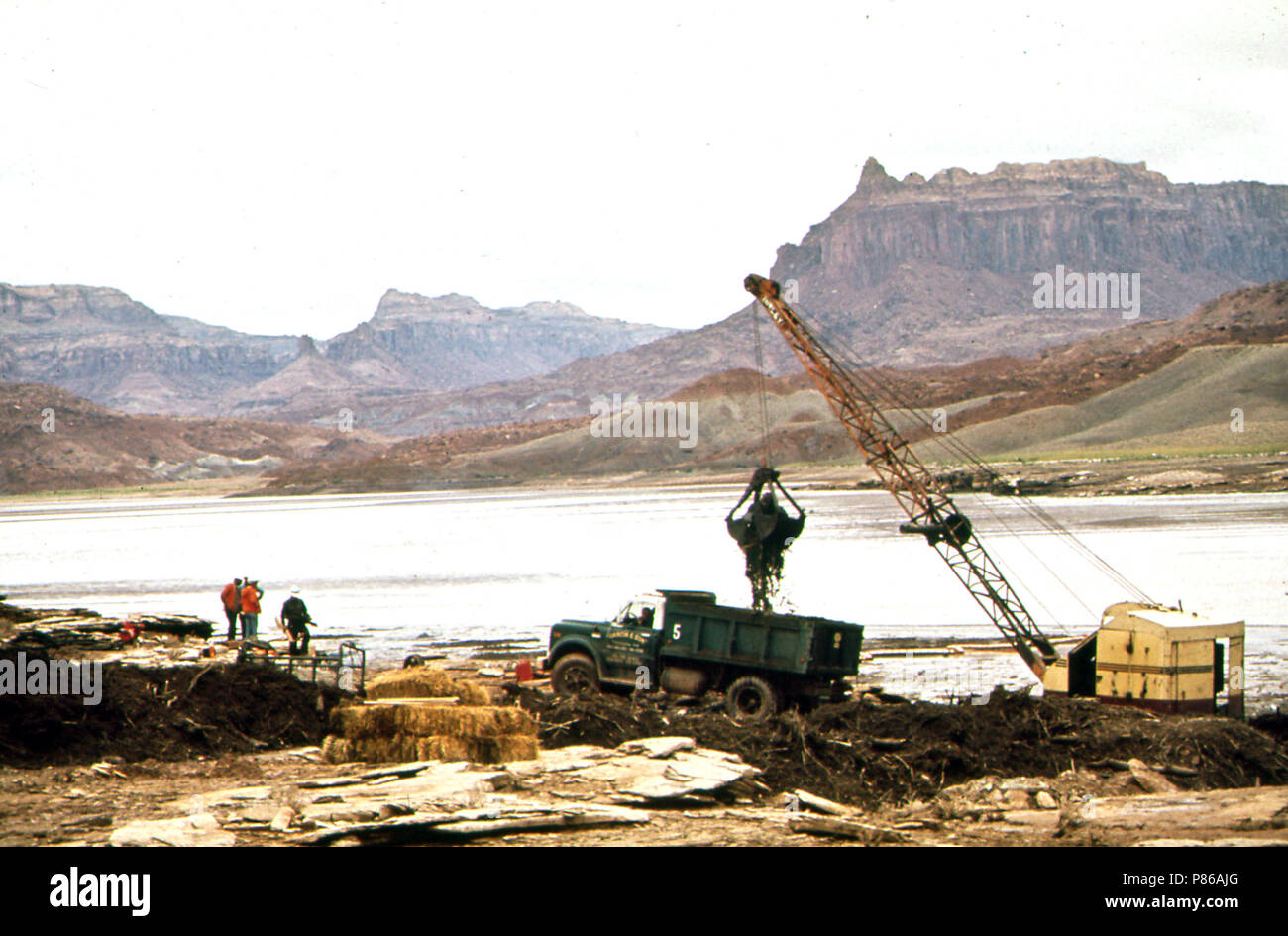 Dragline Basket and Claim Shell Bucket Are Used to Scoop Oil - Laden Debris from Log Boom on the San Juan River, 10 1972 Stock Photo