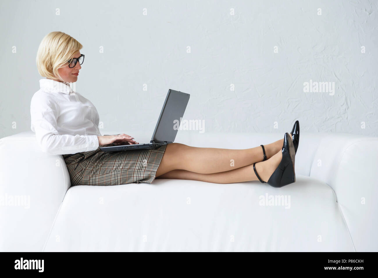 Stylish blonde businesswoman wears eyeglasses sitting on the white stylish leather sofa working with laptop on knees - Stock Image