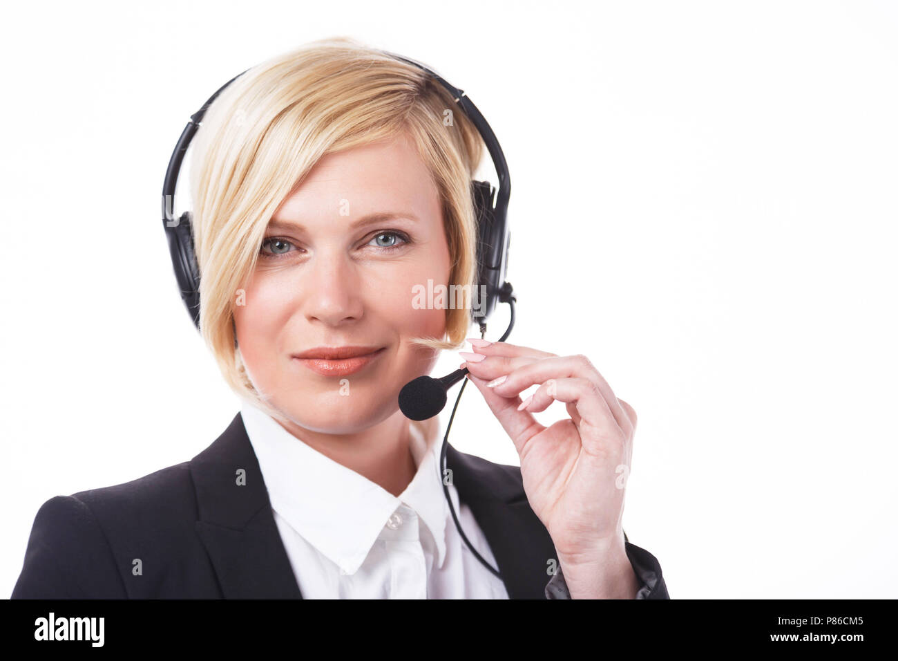 Beautiful smiling call center operator, blonde woman dressed in black jacket before white background with copyspace - Stock Image