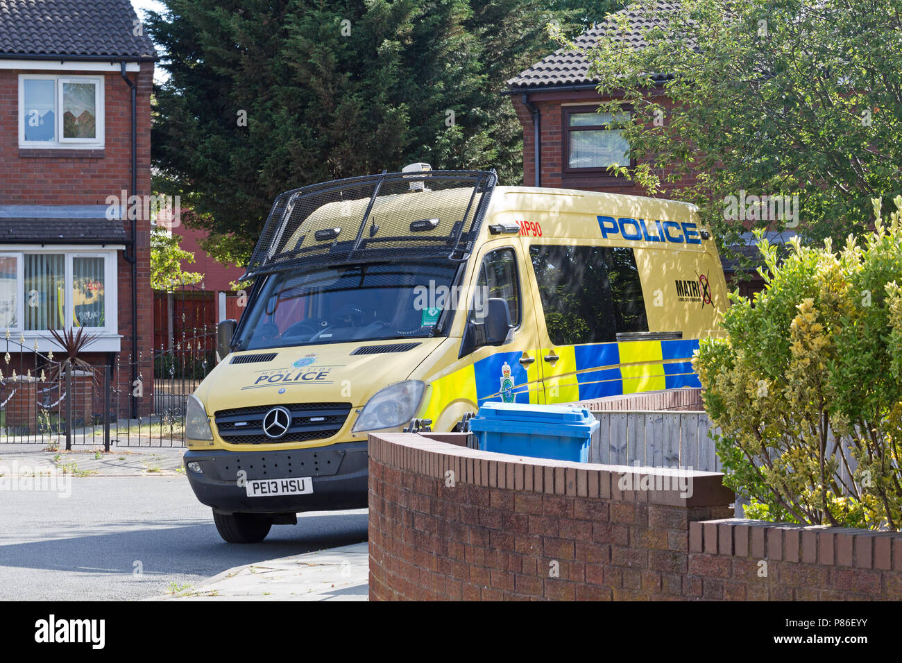 Liverpool, UK. 9th July 2018. Bomb disposal unit and Matrix police officers search a house in Micawber Close in the Toxtheth district of Liverpool. Merseyside Police confirm a suspicious package has been found at the property. Police have issued a statement: 'We are currently in attendance at a property in Toxteth.Officers executed a firearms warrant at Micawber Close at around 11.40pm on Saturday, 7th July, and following a search of the property have located a suspicious package, EOD have been called to the scene'. Credit: Ken Biggs/Alamy Live News. - Stock Image