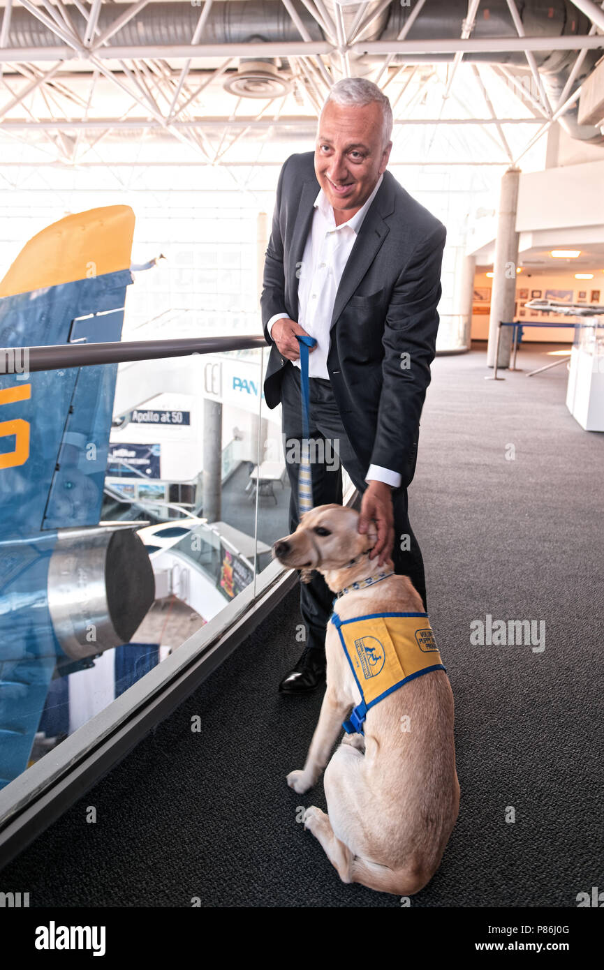 Garden City, New York, USA. 21st June, 2018. NASA space shuttle astronaut MIKE MASSIMINO poses with dog from Canine Companions for Independence, a Medford organization, brought by Volunteer Puppy Raiser Florence Scarinci, after the museum's Members Meet & Greet before Massimino's free lecture in JetBlue Sky Theater Planetarium at the Cradle of Aviation's Museum, part of the museum's Countdown to Apollo at 50, celebrating 50th anniversary of Apollo 11 moon landing on July 20, 1969. Credit: Ann Parry/ZUMA Wire/Alamy Live News - Stock Image