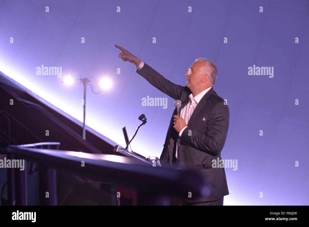 Garden City, New York, USA. 21st June, 2018. Former NASA space shuttle astronaut MIKE MASSIMINO, a Long Island native, is at podium on stage as he points his finger upward while giving free lecture in the JetBlue Sky Theater Planetarium at the Cradle of Aviation Museum. Credit: Ann Parry/ZUMA Wire/Alamy Live News - Stock Image