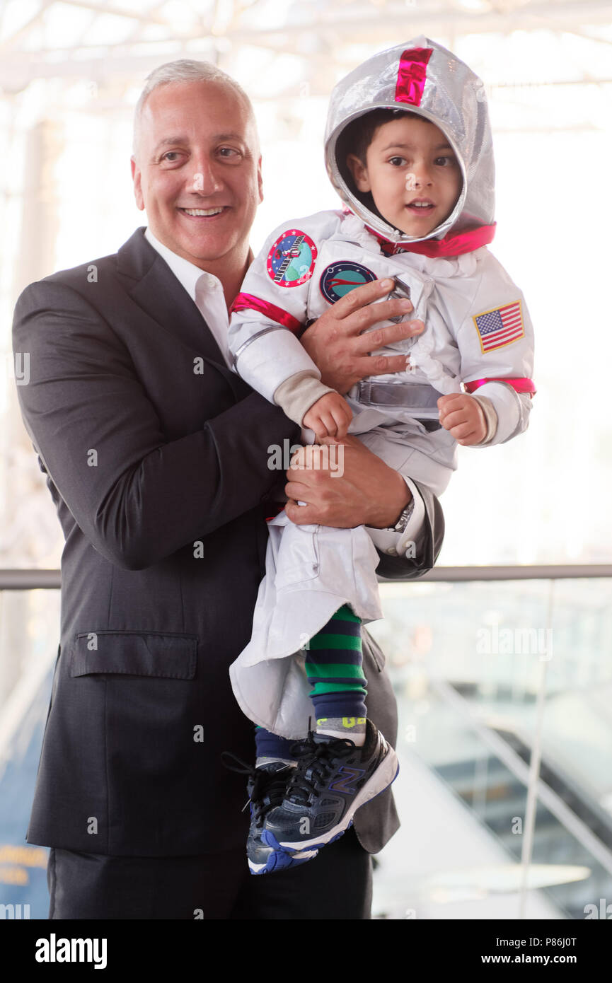 Garden City, New York, USA. 21st June, 2018. NASA space shuttle astronaut MIKE MASSIMINO poses holding GIOVANNI, a 3 1/2 year old boy wearing a space suit costume, from Manhasset, before the former astronaut gave a free lecture at the Cradle of Aviation Museum. Credit: Ann Parry/ZUMA Wire/Alamy Live News - Stock Image