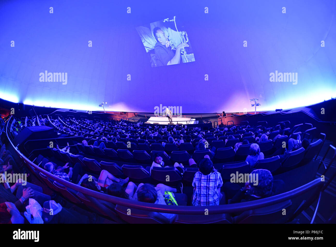 Garden City, New York, USA. 21st June, 2018. NASA space shuttle astronaut MIKE MASSIMINO, a Long Island native, is on stage giving free lecture to full house audience in the JetBlue Sky Theater Planetarium at the Cradle of Aviation Museum. Photo projected on planetatium dome wall was taken when Massimino was sending the first ever tweet from space. Credit: Ann Parry/ZUMA Wire/Alamy Live News - Stock Image