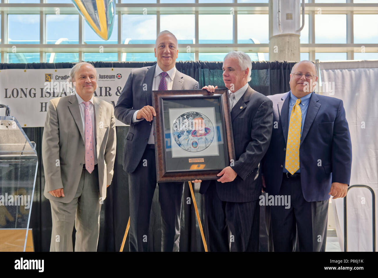 Garden City, New York, USA. 21st June, 2018. On stage, L-R, JOSHUA STOFF, Curator of Cradle of Aviation Museum; former NASA astronaut MICHAEL MASSIMINO; ANDREW PARTON the Executive Director of CAM; and GREG SANTI the Human Resources Manager at Curtiss Wright, pose with official illustration of Long Island Air & Space Hall of Fame inductee Massimino at 10th Annual Luncheon at Cradle of Aviation. Credit: Ann Parry/ZUMA Wire/Alamy Live News - Stock Image