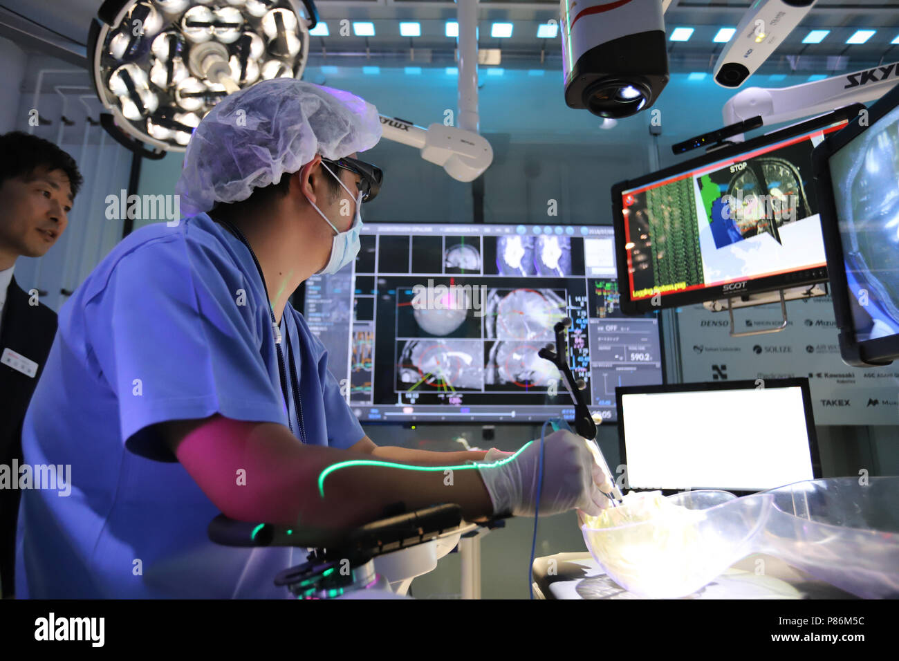"""Tokyo, Japan. 9th July, 2018. A brain surgeon checks monitors and demonstrates the prototype model of the smart surgery room """"Super Cyber operating Theater (SCOT)"""" at a laboratory of the Tokyo Women's Medical University (TWMU) in Tokyo on Monday, July 9, 2018. TWMU, Shinshu University and Japanese electriocs companies such as Denso and Hitachi developed the smart surgery room where all electronics devices such as MRI, operating microscope, electrosurgical knife and communication devices are linked by Denso's OPeLINK system. Credit: Yoshio Tsunoda/AFLO/Alamy Live News Stock Photo"""