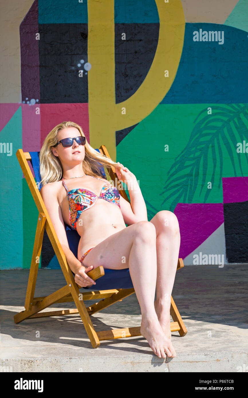 Bournemouth, Dorset, UK. 10th July 2018. UK weather: after a cloudy start, another hot sunny day. Model Leanne Cable enjoys the sunshine at Alum Chine beach. Credit: Carolyn Jenkins/Alamy Live News - Stock Image