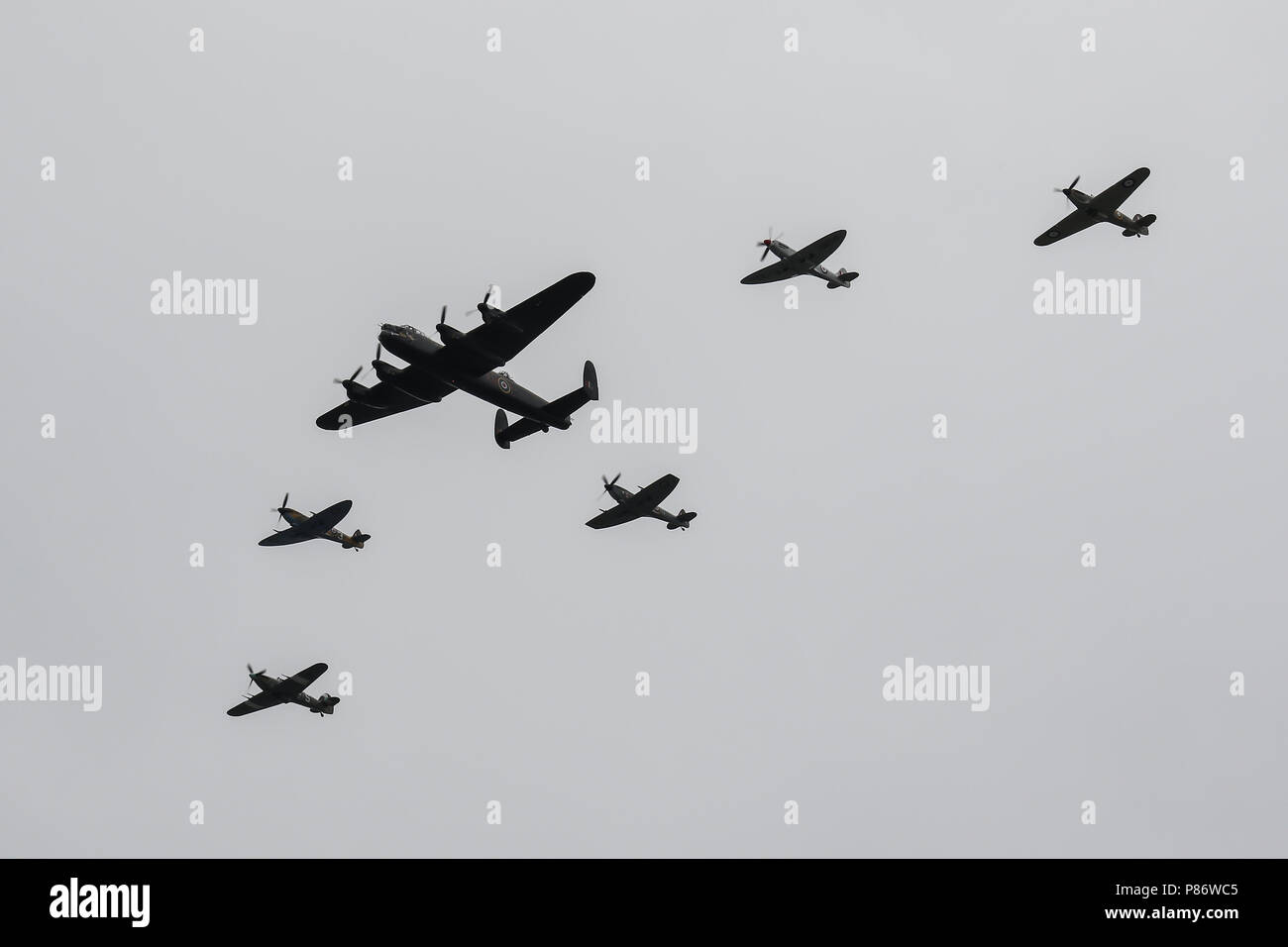 London, UK. 10th July 2018. The Royal Air Force's Battle of Britain Memorial Flight pass over London, with the Avro Lancaster, Two Hawker Hurricanes and three Supermarine Spitfires during the RAF100 Flypast Credit: James Hancock/Alamy Live News - Stock Image