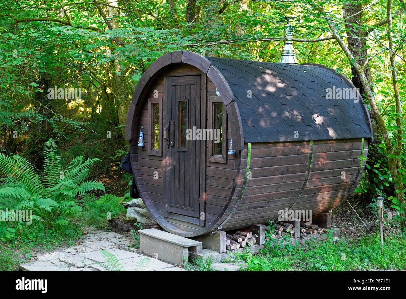 Exterior view of a wooden barrel shaped sweat lodge in a woodland landscape by a stream for bathing in a rural Welsh valley Wales UK  KATHY DEWITT - Stock Image