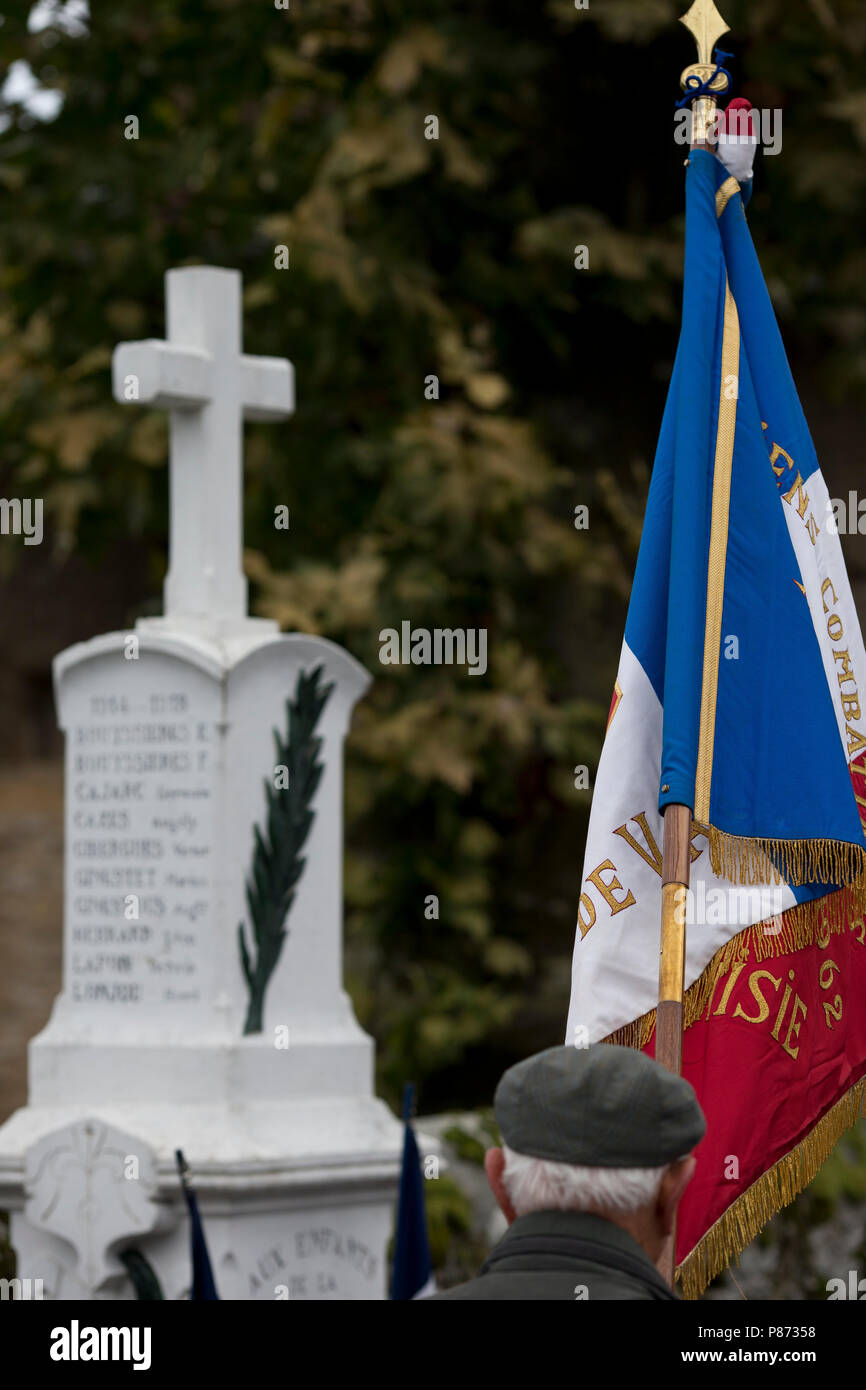 A  French veteran holds his regimental flag on Armistice Day before the war memorial in St Martial, Varen, Tarn et Garonne, Occitanie, France, Europe - Stock Image