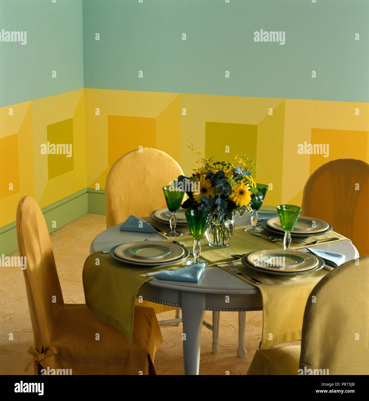 Yellow Loose Covers On Chairs At Small Painted Table Set For Lunch