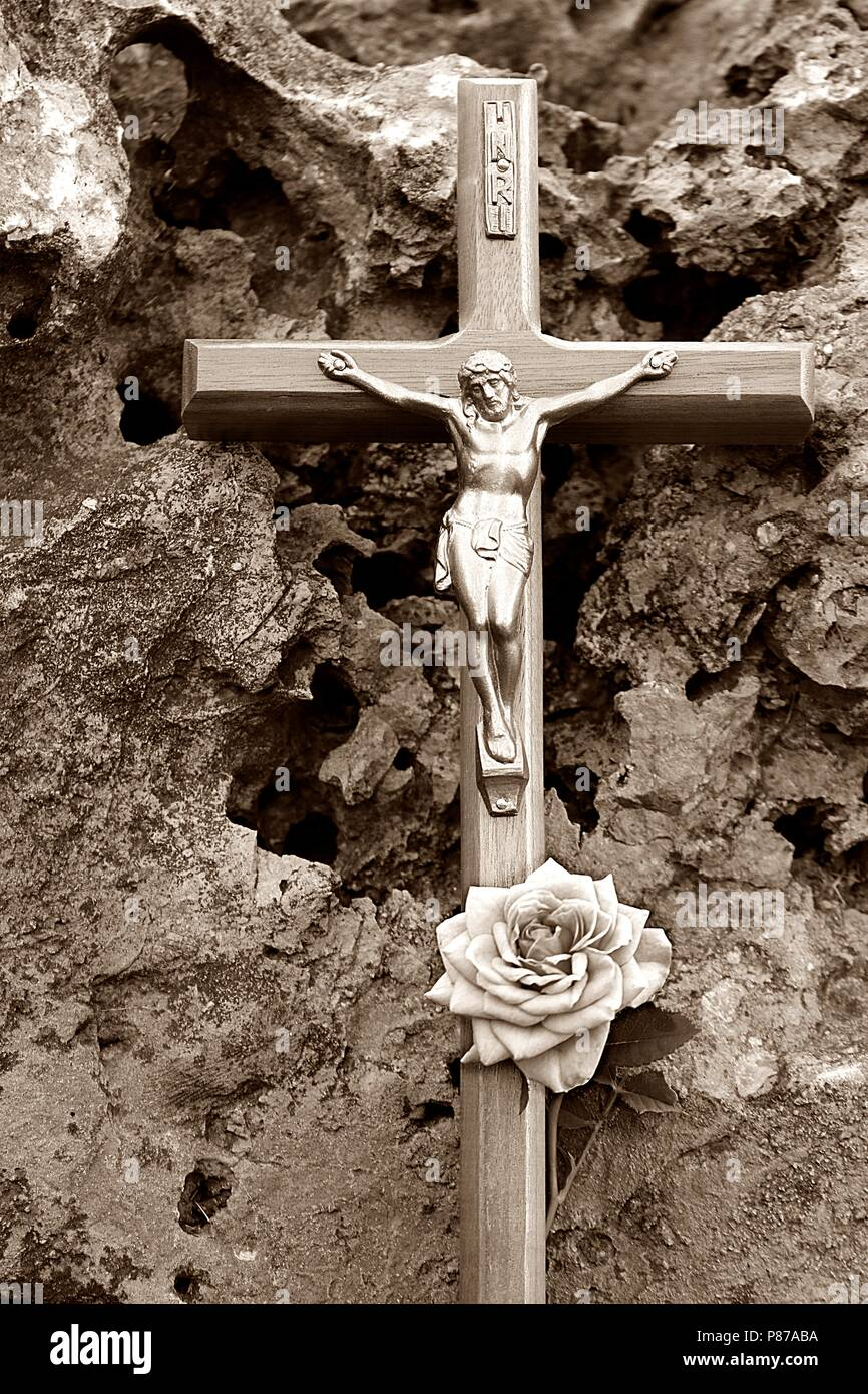 Crucifix on a porous rock with a rose in sepia tones - Stock Image