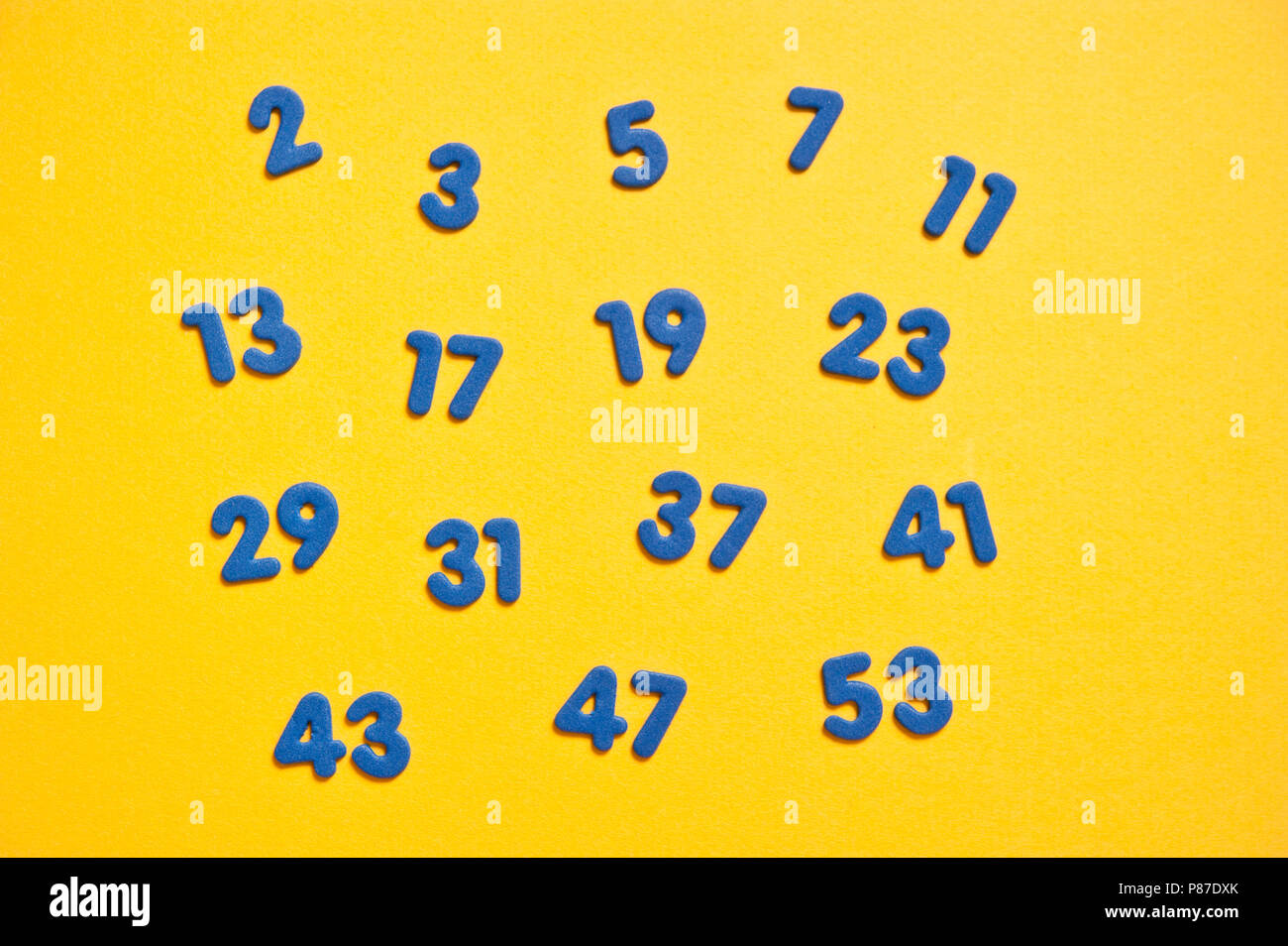 first sixteen prime numbers, blue on yellow - Stock Image