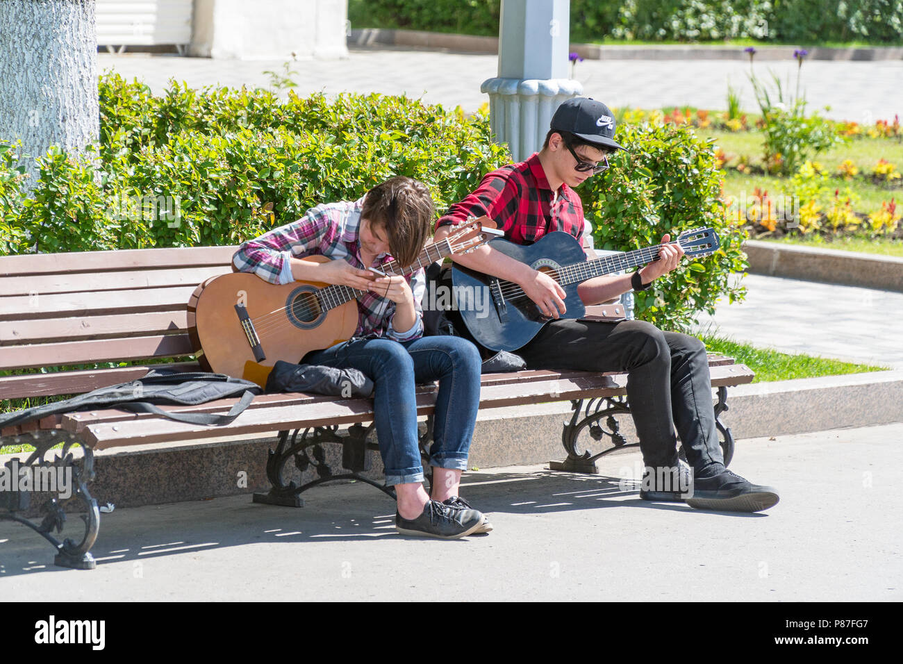 SAMARA, RUSSIA - JUNE 21, 2018: Two young street musicians with guitars on a Park bench - Stock Image