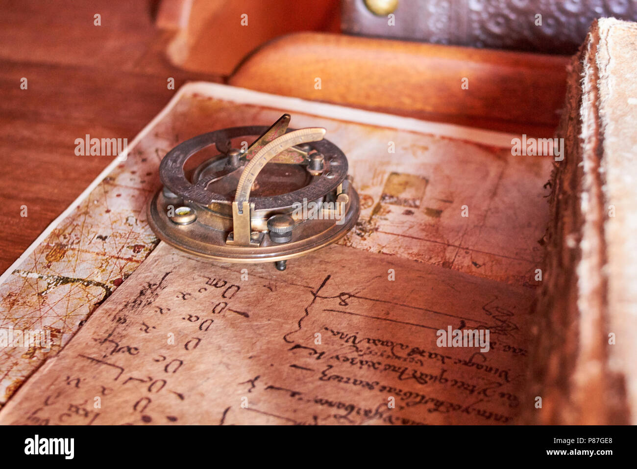 Old sailboat desk with and old book with aged paper - Stock Image